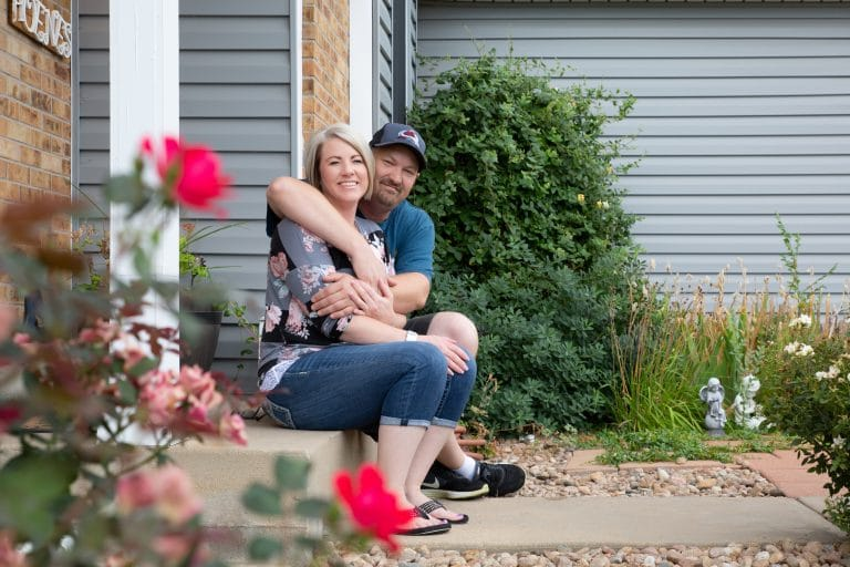 a happy couple sitting on the porch of their beautiful home with siding installed by Colorado Siding Repair