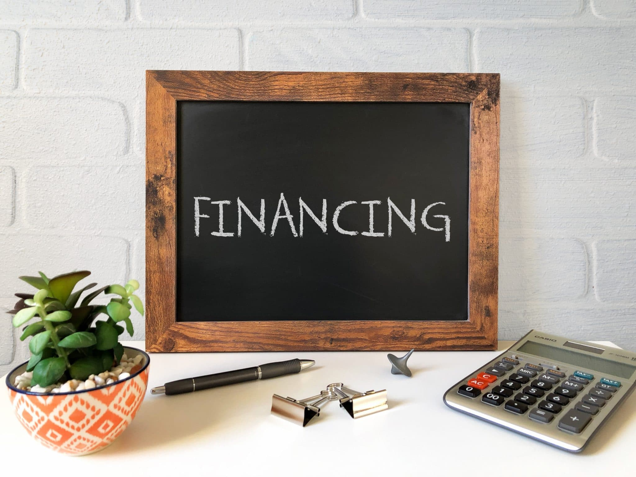 the word 'financing' written on a chalkboard that is sitting on a desk with a calculator and a pen