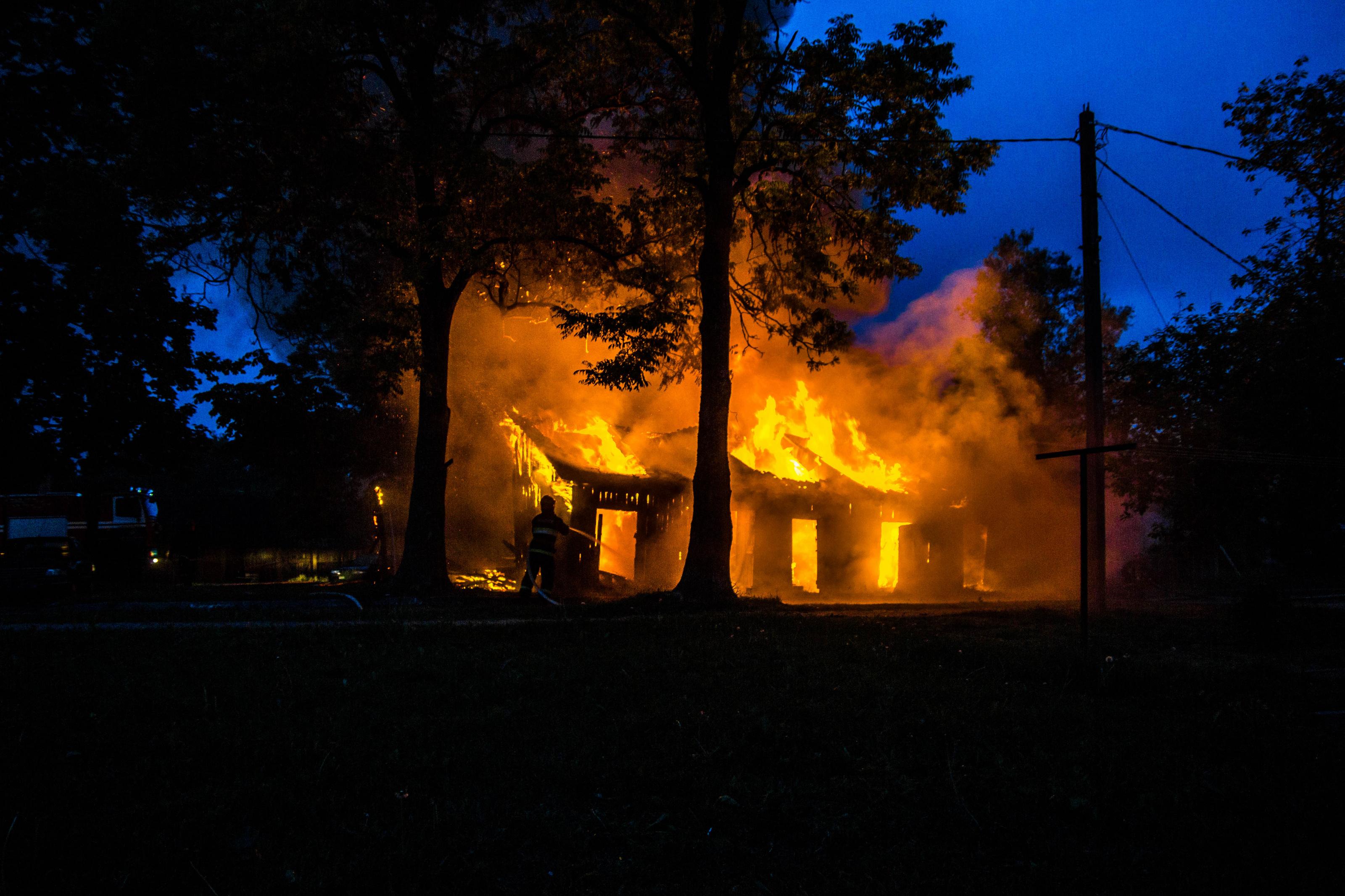 Natural disaster, fire of a wooden house in the forest. Firefighters extinguish the flame.